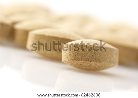 Close-up of nutritional supplement pills on white background.