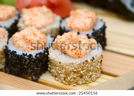 Close-up of of sushi on wood plate.