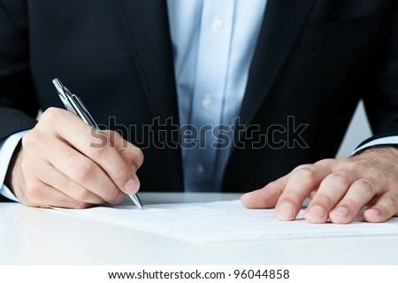 Close up of office worker filling documents