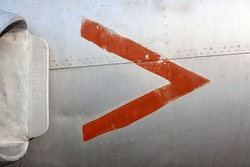 Close up of old aircraft aluminum panel with red arrow.