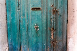 Close up of old blue teal painted door with round door handle, knocker and letter box