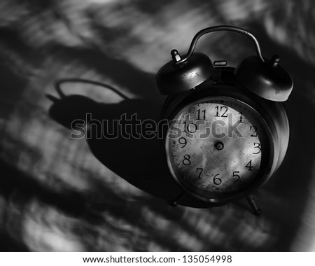 close-up of old broken alarm clock without clock hands on dark background with copy space for your text