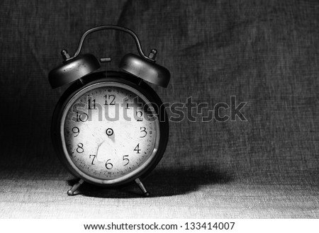 close-up of old broken alarm clock without clock hands on textile background with copy space for your text