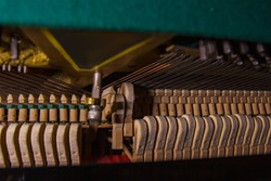 Close up of old broken dusty piano from the inside. Hammers in abandoned piano striking strings. Music playing from the ancient ruined piano