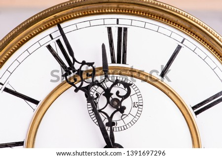 Close-up of old clock face with roman numerals, about midnight twelve