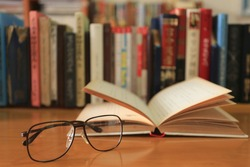 Close-up of old glasses on a reading table Open books and stack of books into the background selective focus and shallow depth of field