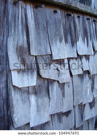 Close up of old grey weathered wooden shingle tiles detailing the wooden dowel pegs