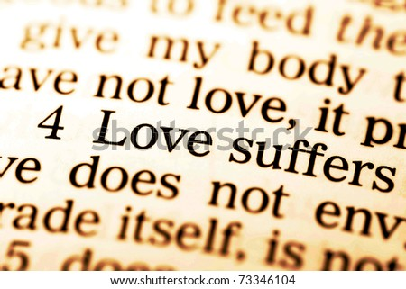 "Close up of old Holy bible book, The word ""Love suffers""."