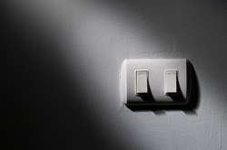 Close up of old light switch with sunlight and shadow on white wall with texture in the dark. turn on and turn off, copy space.