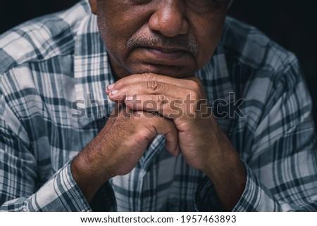 Close-up of old man praying alone in hope.