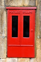 close up of old metal, red painted postage stamp box with black panels and key hole set in stone wall outside