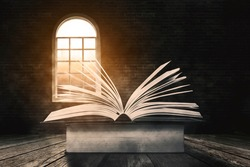 Close up of old open book with flipped pages on a stack of books with window illuminating into the dark room