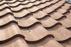 Close up of old roof tiles hand made terracotta colour made of  clay laid on roof showing the curve pattern of the brick on the surface in the Summer sunshine exterior on historic building