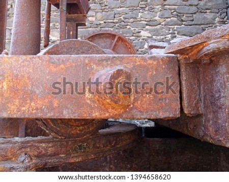 close up of old rusty crane mechanism in the old coal docks in funchal Madeira against a stone wall