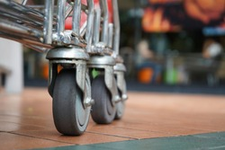 Close-up of old shopping cart wheels, Concept of shopping