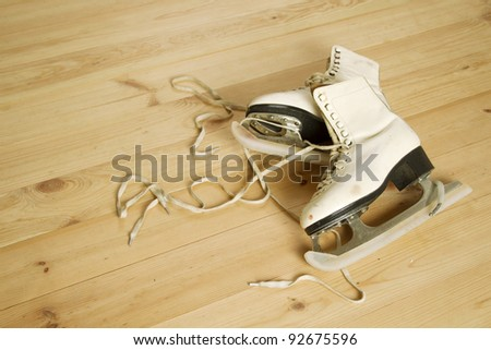 Close-up of old skates for figure skating are on a wooden floor