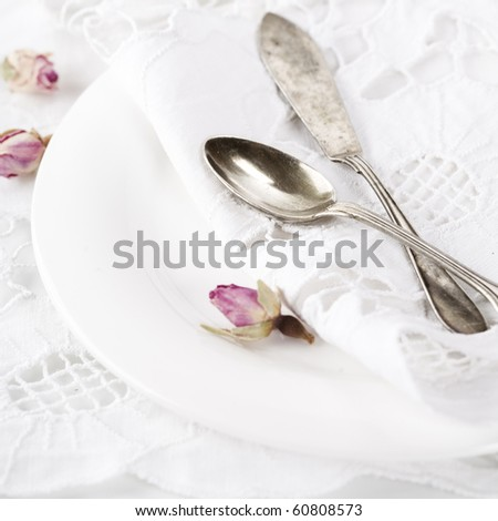 Close-up of old spoons on plate with linen napkin and dry roses