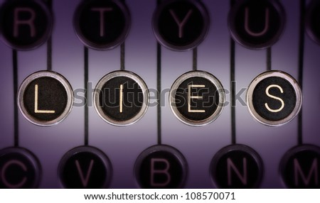 Close up of old typewriter keyboard with scratched chrome keys that spell out LIES. Lighting and focus are centered on LIES.