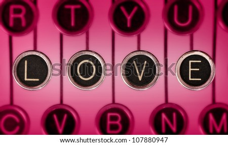 Close up of old typewriter keyboard with scratched chrome keys that spell out LOVE. Lighting and focus are centered on LOVE.