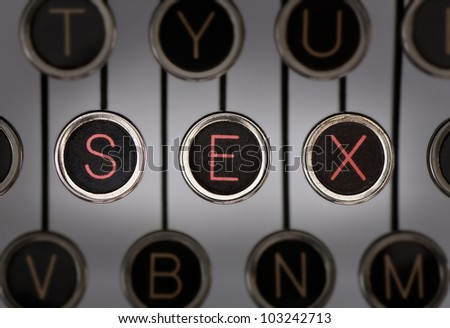 """Close up of old typewriter keyboard with scratched chrome keys with black centers and white letters. Lighting and focus are centered on for keys spelling out """"SEX""""."""