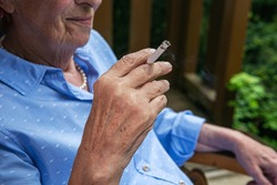 close-up of old woman smoking a cigarette