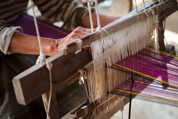 Close up of old woman weaving blue and white pattern on loom