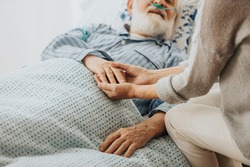 Close-up of older dying man holding his wife's hands