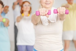 Close-up of older woman exercising shoulders with dumbbells