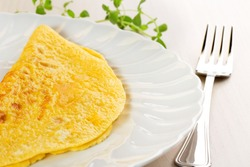 close up of omelette and fork on table