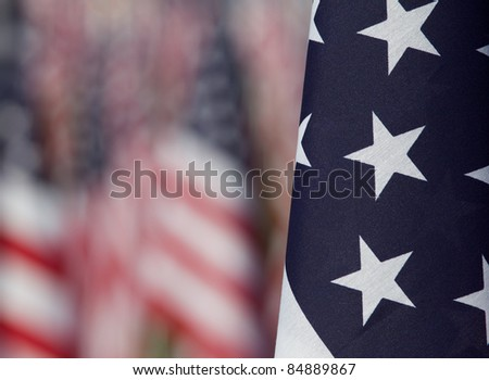 Close-up of  one flag with other flags purposely blurred in the background. Each flag was designed to represent a person who died in the terrorist attacks on 9/11/2001.