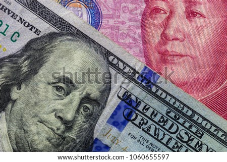Close up of one hundred Dollar banknote over a 100 Yuan banknote with focus on portraits of Benjamin Franklin and Mao Tse-tung/USA vs China trade war concept