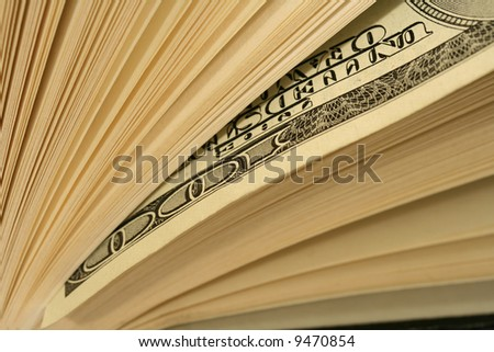 Close-up of one hundred dollars bill between pages of book. Book looking as a stack of bills