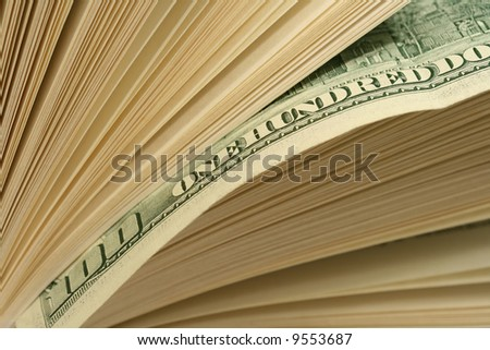 Close-up of one hundred dollars bill between pages of book. Pages of book looking as a stack of bills