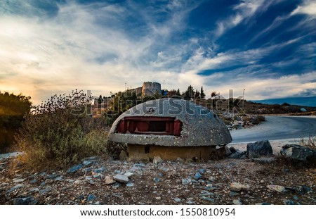 Close-up of one of the countless military concrete bunkers or pillboxes in the southern Albania built by communist government of Enver Hoxha. Lekuresi Castle on background. Saranda, Albania.