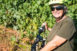 Close up of one smiling senior woman with white hair in the middle of the bunches of grapes. E bike close to her, for healthy lifestyle. One happy people.Green vineyard in background.
