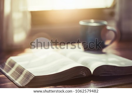 close up of open bible with acup of coffee for morning devotion on wooden table with window light #1062579482