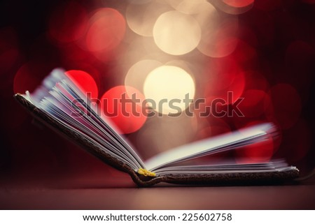 Close up of open book against defocused lights background, shallow depth of field