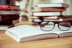 Close up of open book with eyeglasses on wooden desk, Soft focus, Vintage tone