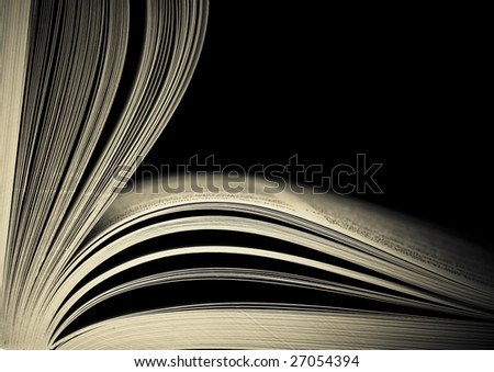 Close-up of opened book pages against black background. Space for text. Shallow DOF.