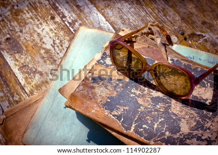 Close-up of opened book pages and glasses against vintage background/Vintage books with reading glasses in an used bookstore