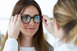 Close-up of optometrist and pretty young woman choosing eyeglasses in optics.