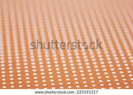 Close up of orange and white spotted textile