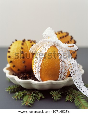 Close up of oranges pinned with cloves and wrapped in lace