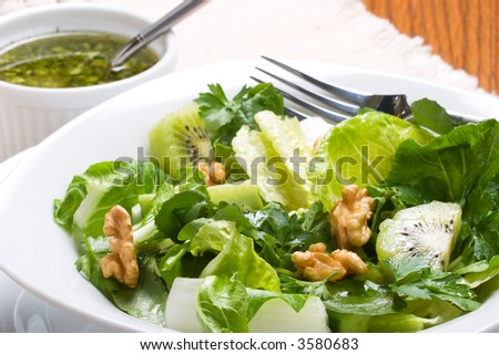Close up of organic green salad with walnut and lime-pepper dressing