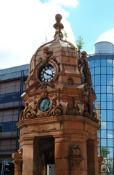Close Up of Ornately Carved 19th Century Public Stone Cupola and Clock on Modern City Street