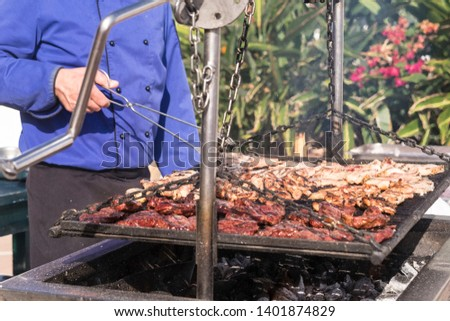 Close up of outdoor big barbecue bbq grill for restaurant or catering business concept - fresh meat and tasty food for people - man cooking outdoor with fire