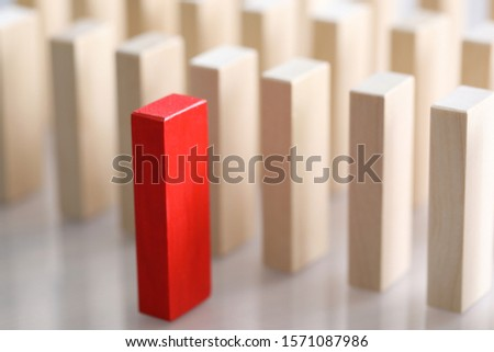 Close-up of outstanding red wooden brick standing ahead of light similar blocks. Lots of bars placed in the line. Leadership ideas and uniqueness concept