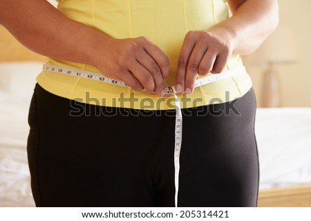 Close Up Of Overweight Woman Measuring Waist