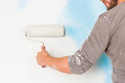 Close up of painter arm in splattered paint shirt painting a wall with paint roller; copy space