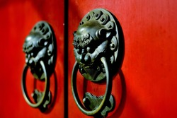 Close up of pair of antique brass Chinese lion door knockers on a colorful red lacquered temple door in Singapore, Chinatown